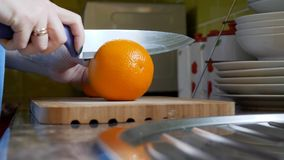 Θηλυκά χέρια που κόβουν το πορτοκάλι στον ξύλινο πίνακα πινάκων στην κουζίνα Στοκ εικόνες με δικαίωμα ελεύθερης χρήσης