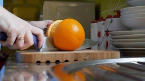 Θηλυκά χέρια που κόβουν το πορτοκάλι στον ξύλινο πίνακα πινάκων στην κουζίνα Στοκ Εικόνα