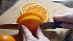 Θηλυκά χέρια που κόβουν το πορτοκάλι στον ξύλινο πίνακα πινάκων στην κουζίνα Στοκ Φωτογραφίες