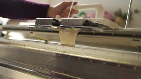 Θηλυκά χέρια που λειτουργούν στην υφαίνοντας μηχανή στο εργαστήριο Πλέκοντας μάλλινο ύφασμα φιλμ μικρού μήκους