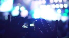 Θηλυκά χέρια που παίρνουν τις εικόνες στο τηλέφωνο στη συναυλία, που χρησιμοποιεί τη συσκευή για να σώσει τις μνήμες απόθεμα βίντεο