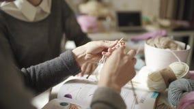 Θηλυκά χέρια που πλέκουν το μάλλινο νήμα βελόνων στο σπίτι Γυναίκα που μαθαίνει να πλέκει απόθεμα βίντεο