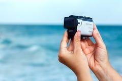Θηλυκά χέρια που πυροβολούν το βίντεο με το έκκεντρο X3000 δράσης της Sony σε μια θάλασσα στοκ εικόνες