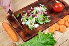 Θηλυκά χέρια που τεμαχίζουν την πράσινη σαλάτα, που μαγειρεύει τη σαλάτα λαχανικών στο ξύλινο υπόβαθρο Στοκ Φωτογραφία