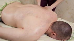 Θηλυκά χέρια που τρίβουν τον ώμο ενός αρσενικού πελάτη στη SPA Υγεία, χαλάρωση φιλμ μικρού μήκους