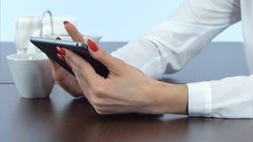 Θηλυκά χέρια χρησιμοποιώντας την ταμπλέτα και κρατώντας το φλυτζάνι καφέ στοκ εικόνες