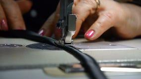 Κινηματογράφηση σε πρώτο πλάνο του ράφτη Θηλυκά χέρια seamstress στην εργασία Ράψιμο με μια ράβοντας μηχανή με το μαύρο υλικό o απόθεμα βίντεο