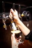 Θηλυκά bartender χέρια που χύνουν τη σκοτεινή μπύρα από τη βρύση στο φραγμό στοκ φωτογραφία