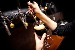 Θηλυκά bartender χέρια που χύνουν τη σκοτεινή μπύρα από τη βρύση στο φραγμό στοκ φωτογραφία με δικαίωμα ελεύθερης χρήσης
