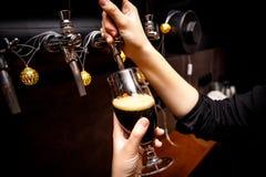 Θηλυκά bartender χέρια που χύνουν τη σκοτεινή μπύρα από τη βρύση στο φραγμό στοκ φωτογραφίες με δικαίωμα ελεύθερης χρήσης