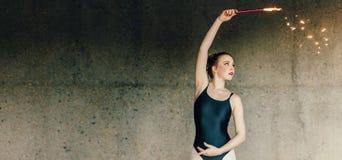 Θηλυκές κινήσεις χορού άσκησης χορευτών μπαλέτου που χρησιμοποιούν ένα πυροτέχνημα στοκ εικόνα με δικαίωμα ελεύθερης χρήσης