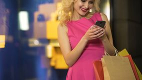 Θηλυκές shopaholic τιμές ελέγχου των αγορών της στα σε απευθείας σύνδεση καταστήματα, κινητό app απόθεμα βίντεο