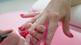 Θηλυκή άποψη κινηματογραφήσεων σε πρώτο πλάνο μανικιούρ χεριών Ηλικίας γυναικείο χέρι στη διαδικασία μανικιούρ φιλμ μικρού μήκους
