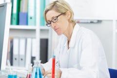 Θηλυκή έκθεση γραψίματος επιστημόνων σχετικά με τα πειράματα επιστήμης στοκ φωτογραφία