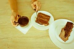Θηλυκή εκμετάλλευση χεριών στο μακρύ κουτάλι ένα κομμάτι του κέικ στον πίνακα στο ασβέστιο Στοκ φωτογραφία με δικαίωμα ελεύθερης χρήσης