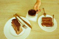Θηλυκή εκμετάλλευση χεριών στο μακρύ κουτάλι ένα κομμάτι του κέικ στον πίνακα στο ασβέστιο Στοκ Εικόνες