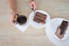 Θηλυκή εκμετάλλευση χεριών στο μακρύ κουτάλι ένα κομμάτι του κέικ στον πίνακα στον καφέ Στοκ Εικόνες
