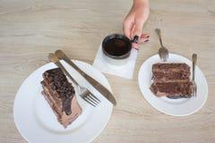 Θηλυκή εκμετάλλευση χεριών στο μακρύ κουτάλι ένα κομμάτι του κέικ στον πίνακα στον καφέ Στοκ φωτογραφία με δικαίωμα ελεύθερης χρήσης