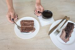 Θηλυκή εκμετάλλευση χεριών στο μακρύ κουτάλι ένα κομμάτι του κέικ στον πίνακα στον καφέ Στοκ εικόνα με δικαίωμα ελεύθερης χρήσης