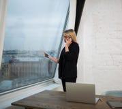 Θηλυκή εκτελεστική περίληψη ανάγνωσης διευθυντή κατά τη διάρκεια της κλήσης κινητών τηλεφώνων Στοκ Εικόνες