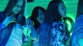 Θηλυκή επιχείρηση με τους χορούς ποτών colorfuls στη πίστα χορού στη μοντέρνη λέσχη νύχτας απόθεμα βίντεο