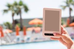 Θηλυκή ηλεκτρονική συσκευή εκμετάλλευσης χεριών για την ανάγνωση στοκ εικόνες με δικαίωμα ελεύθερης χρήσης