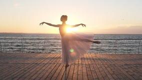 Θηλυκή κατάρτιση χορευτών μπαλέτου υπαίθρια σε ένα ξύλινο ανάχωμα κοντά στη θάλασσα Το κορίτσι έντυσε σε ένα άσπρο tutu Ο ήλιος λ απόθεμα βίντεο