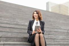 Θηλυκή καυκάσια συνεδρίαση διευθυντών στα σκαλοπάτια με την ταμπλέτα και την εργασία Στοκ Φωτογραφίες