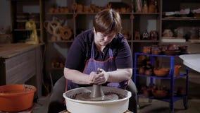 Θηλυκή κύρια συνεδρίαση ποδιών φθοράς και διαμόρφωση clayware στη ρόδα αγγειοπλαστών ` s στο εργαστήριο φιλμ μικρού μήκους