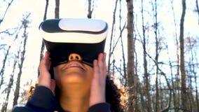 Θηλυκή νέα γυναίκα εφήβων κοριτσιών αφροαμερικάνων Biracial που χρησιμοποιεί την κάσκα εικονικής πραγματικότητας VR σε ένα δασικό φιλμ μικρού μήκους