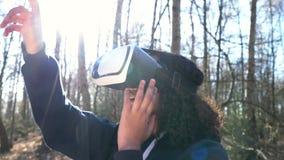 Θηλυκή νέα γυναίκα εφήβων κοριτσιών αφροαμερικάνων Biracial που χρησιμοποιεί την κάσκα εικονικής πραγματικότητας VR σε ένα δασικό απόθεμα βίντεο