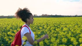 Θηλυκή νέα γυναίκα εφήβων κοριτσιών που με το κόκκινο σακίδιο πλάτης και το μπουκάλι νερό στον τομέα των κίτρινων λουλουδιών φιλμ μικρού μήκους