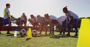 Θηλυκή ομάδα ποδοσφαίρου που εξαντλείται μετά από να εκπαιδεύσει στο γήπεδο ποδοσφαίρου 4K φιλμ μικρού μήκους