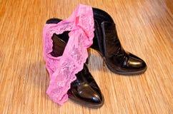 Θηλυκή, ρόδινη, χρησιμοποιημένη σειρά κιλοτών στα μαύρα παπούτσια δέρματος διπλωμάτων ευρεσιτεχνίας φετίχ στοκ φωτογραφία με δικαίωμα ελεύθερης χρήσης