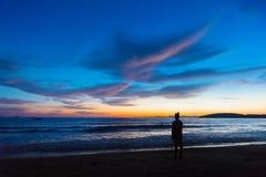 Θηλυκή στάση σκιαγραφιών στην παραλία κατά τη διάρκεια του ηλιοβασιλέματος Στοκ Εικόνες