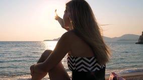 Θηλυκή σύλληψη The Sun χεριών στη συνεδρίαση ουρανού στη θάλασσα παραλιών απόθεμα βίντεο