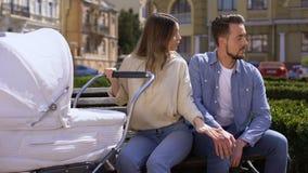 Θηλυκή ταλάντευση νεογέννητη στη μεταφορά που ανατρέπεται στο σύζυγο που εξετάζει τις γυναίκες στην οδό απόθεμα βίντεο