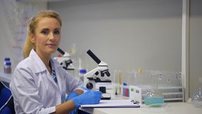 Θηλυκή τοποθέτηση επιστημόνων για τη κάμερα εργαζόμενων στο εργαστήριο φιλμ μικρού μήκους