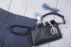 Θηλυκή τσάντα ουσίας μόδας, παντελόνι, γυαλιά ηλίου, στιλβωτική ουσία καρφιών, κόσμημα μαργαριταριών στο άσπρο ξύλινο υπόβαθρο Στοκ φωτογραφία με δικαίωμα ελεύθερης χρήσης