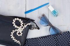 Θηλυκή τσάντα ουσίας μόδας, παντελόνι, γυαλιά ηλίου, στιλβωτική ουσία καρφιών, κόσμημα μαργαριταριών στο άσπρο ξύλινο υπόβαθρο Στοκ εικόνες με δικαίωμα ελεύθερης χρήσης