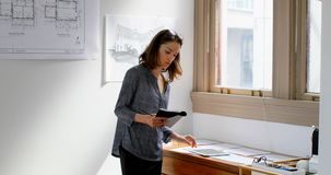 Θηλυκοί αρχιτέκτονες που χρησιμοποιούν την ταμπλέτα εργαζόμενοι στα σχεδιαγράμματα 4k απόθεμα βίντεο