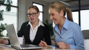 Θηλυκοί διευθυντές που διαβάζουν τις μεγάλες ειδήσεις στο lap-top, που χαίρονται επιτυχές το ξεκίνημα φιλμ μικρού μήκους