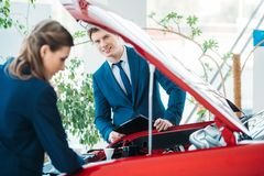 Θηλυκοί και αρσενικοί διευθυντές πωλήσεων μιας αίθουσας εκθέσεως αυτοκινήτων που κοιτάζει κάτω από το ανοικτό αυτοκίνητο στοκ εικόνες με δικαίωμα ελεύθερης χρήσης
