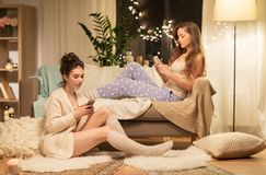 Θηλυκοί φίλοι με τα smartphones στο σπίτι Στοκ Εικόνες