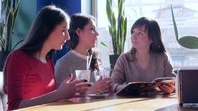 Θηλυκοί φίλοι με το φύλλο cappuccino μέσω των επιλογών στο εστιατόριο απόθεμα βίντεο