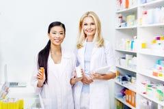 θηλυκοί φαρμακοποιοί με την ψηφιακά ταμπλέτα και το φάρμακο που χαμογελούν στη κάμερα στοκ εικόνες