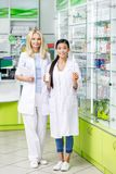 θηλυκοί φαρμακοποιοί με την ψηφιακή ταμπλέτα και φάρμακα που χαμογελούν στη κάμερα στοκ φωτογραφία με δικαίωμα ελεύθερης χρήσης