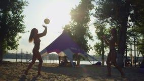 Θηλυκοί φορείς πετοσφαίρισης που παίζουν την πετοσφαίριση στην παραλία απόθεμα βίντεο