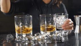 Θηλυκοί bartender κύβοι πάγου μείωσης σε ένα γυαλί με το ουίσκυ σε σε αργή κίνηση Πάγος που πέφτει κάτω από το ράντισμα 15 woman  απόθεμα βίντεο
