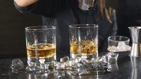 Θηλυκοί bartender κύβοι πάγου μείωσης σε ένα γυαλί με το ουίσκυ σε σε αργή κίνηση Πάγος που πέφτει κάτω από το ράντισμα 15 woman  φιλμ μικρού μήκους